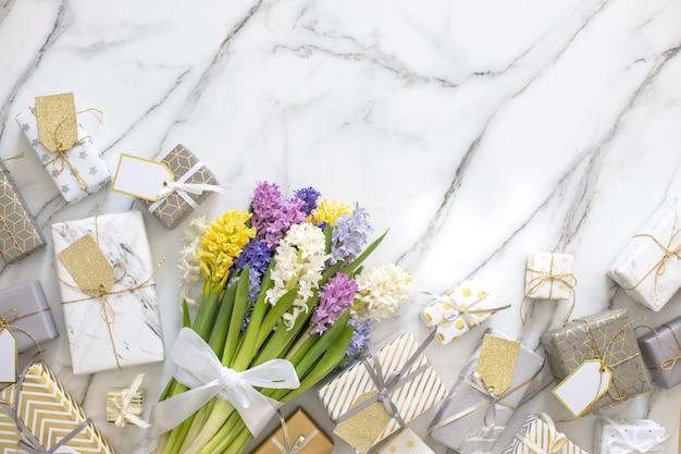 Trendige komposition der draufsicht mit festlich verpackter bandschleife der geschenkboxen, verziert durch blütenblumen