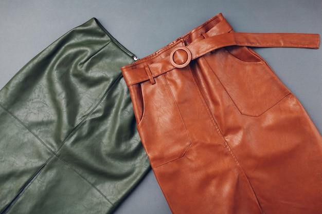 Trendige lederröcke. frühlingskleidung für frauen. stilvolle braune und grüne röcke aus ökologischem material. mode
