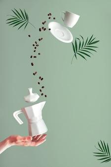 Trendige levitation. fliegende kaffeebohnen und espressotasse mit untertasse. grüne minzwand mit palmblättern, textraum. kaffeemaschine des keramikofens, die auf zeigefinger der weiblichen hand balanciert.