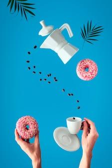 Trendige levitation. fliegende reihe von kaffeebohnen zwischen keramikkaffeemaschine und espressotasse mit untertasse. weibliche hände halten rosa donuts mit zuckerstreuseln. blaue minzwand mit palmblättern.