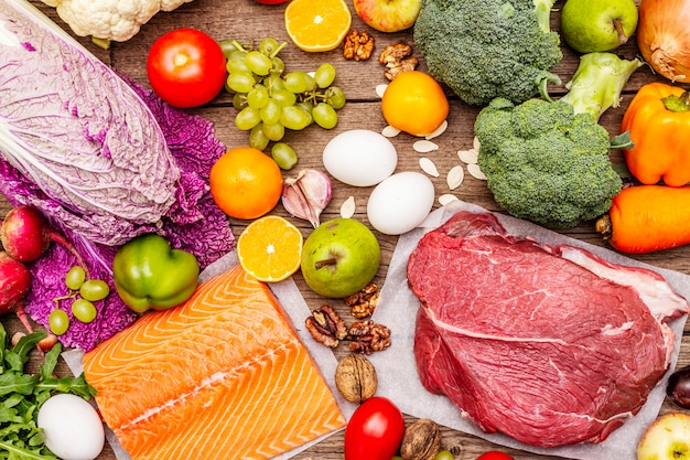 Trendige paläo / pegane ernährung. gesundes ausgeglichenes nahrungsmittelkonzept. set aus frischen produkten, rohem fleisch, lachs, gemüse und obst