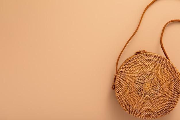 Trendige rattantasche auf naturtonhintergrund. weibliche mode reisekonzept. flache lage, draufsicht, trendiger modestil. öko-design.