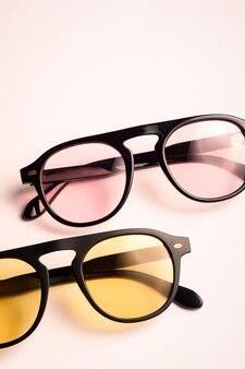 Trendige rosa und gelbe sonnenbrille mit schwarzem rahmen mit glänzender reflektion