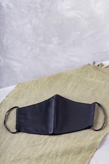 Trendige schutzmaske auf grünem tuch. schwarze gesichtsmaske auf ultimativem grauem hintergrund. speicherplatz kopieren