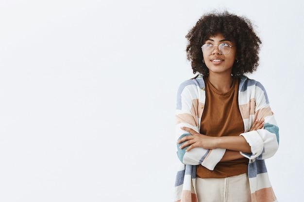 Trendige städtische afroamerikanische mitarbeiterin in transparenten trendigen brillen und outfit händchen haltend gekreuzt auf der brust und blick auf die obere linke ecke mit verträumtem süßem lächeln