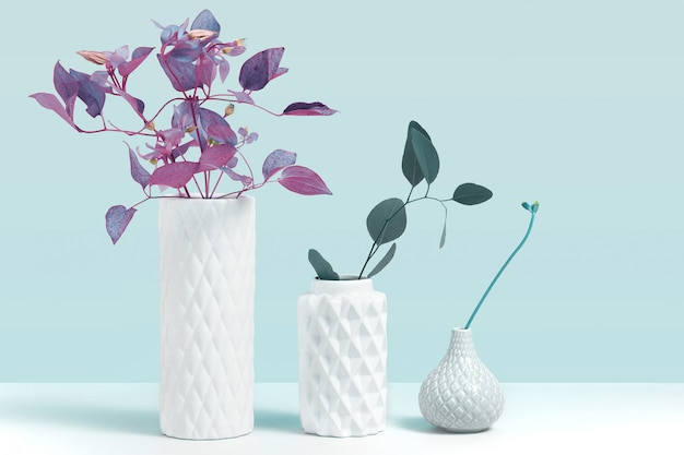 Trendige ultraviolette farbpflanze in vase. modellbild mit zierpflanzen in der modernen weißen keramikvase, die auf grauem tisch gegen blauen hintergrund steht. konzept für blumenladen mit raum für design