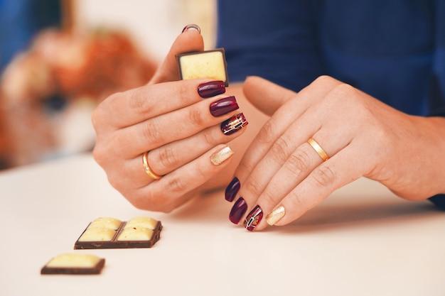 Trendige und schöne maniküre auf weiblichen händen. nägel purpurrot oder burgund in kombination mit goldglanz.