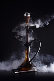 Trendige wasserpfeife mit rauchwolke auf schwarzem hintergrund
