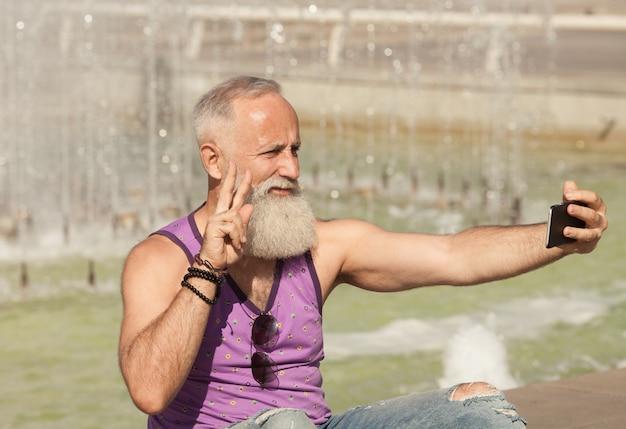 Trendiger älterer mann, der smartphone in der innenstadt im freien verwendet - reifer mode-mann, der spaß mit neuer trendtechnologie hat - tech und freudiges älteres lebensstilkonzept