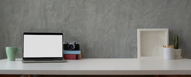 Trendiger arbeitsbereich mit laptop, kaffeetasse, dekorationen und kopierraum