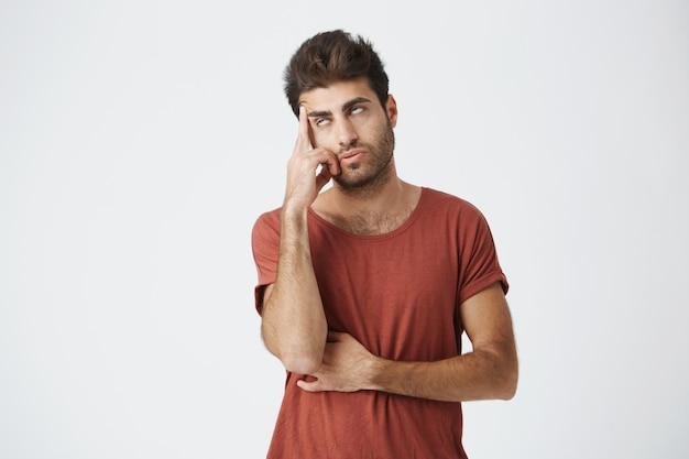 Trendiger bärtiger junger mann, der es satt hat, jemandem geschichten oder vorwürfe anzuhören. er hielt seinen kopf und rollte mit den augen, als er nicht weiter nutzlose gespräche hören wollte