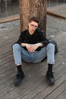 Trendiger europäischer junger mann in vintage-brille in modischer, lässiger denim-kleidung in stylischen turnschuhen