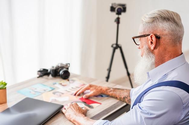 Trendiger fotograf in seinem kreativstudio, der fotos und bilder auswählt. hipster mann bei der arbeit