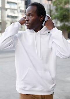 Trendiger hoodie für mann mit brauner hose in der stadt