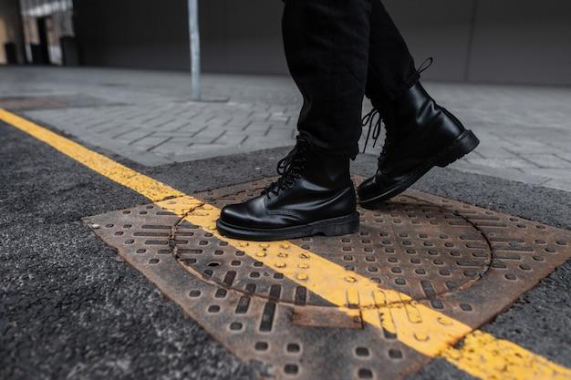 Trendiger junger mann in schwarzen vintage-lederstiefeln in modischen jeans steht auf einer eisernen luke in der stadt. nahaufnahme von männlichen beinen in stilvollen saisonalen schuhen. streetstyle. jugendmode. freizeitschuhe.