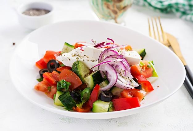 Trendiger salat. griechischer salat mit frischem gemüse, feta-käse und schwarzen oliven. gesunde ausgewogene ernährung.