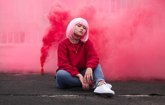 Trendiger teenager, der auf stadtstraße gegen rosa rauch sitzt