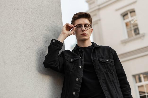 Trendiges amerikanisches mann-mode-modell setzt vintage-brille auf der straße auf. straßenporträt modischer junger mann in stilvoller schwarzer jeansjacke im t-shirt mit frisur in der nähe des weißen gebäudes in der stadt.