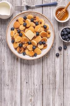 Trendiges frühstück mit mini-pfannkuchen, blaubeeren und schokoladenstückchen, draufsicht.