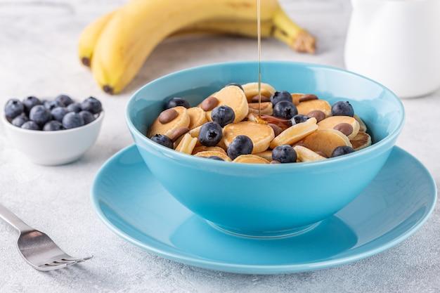 Trendiges frühstück mit mini-pfannkuchen, blaubeeren und schokoladenstückchen, selektiver fokus.