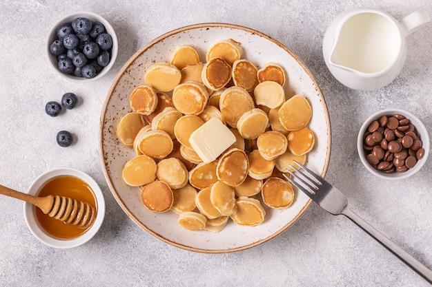 Trendiges frühstück mit mini-pfannkuchen und butter, draufsicht.