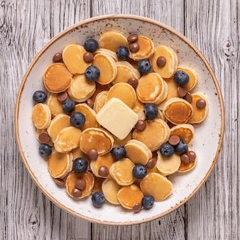 Trendiges frühstück mit minipfannkuchen, blaubeeren und schokoladenstückchen, draufsicht.