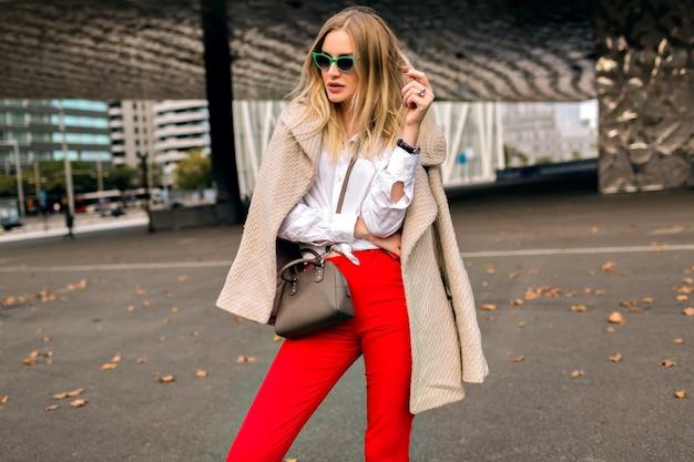 Trendiges herbstmodeporträt der stilvollen jungen frau, die nahe modernes architekturgebäude aufwirft, das hipster-geschäftsoutfit und -mantel, weinlese-sonnenbrille, getönte farben trägt.