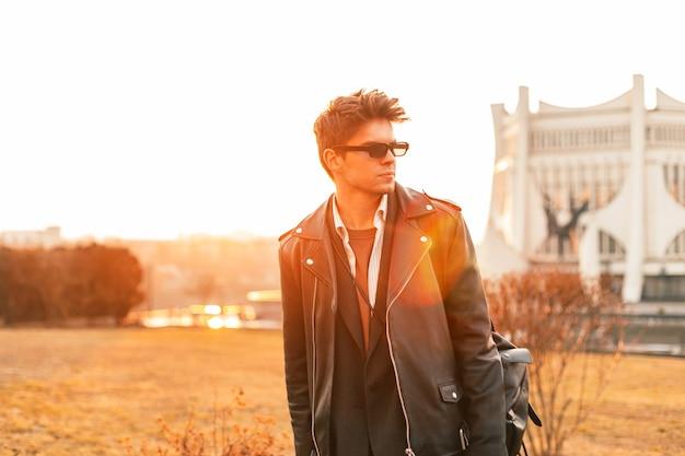 Trendiges junges mannmodell in stilvoller sonnenbrille in modischer schwarzer lederjacke im hemd mit vintage-rucksack posiert abends im freien. attraktiver hipster-typ genießt bei sonnenuntergang orangefarbenes sonnenlicht.