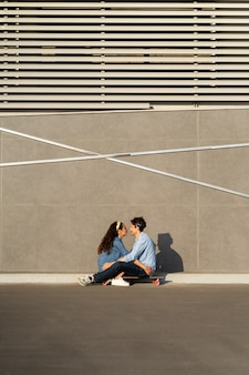 Trendiges junges paar sitzt auf longboard auf sonniger stadtstraße glücklich lächelnde umarmung genießt die zeit zusammen