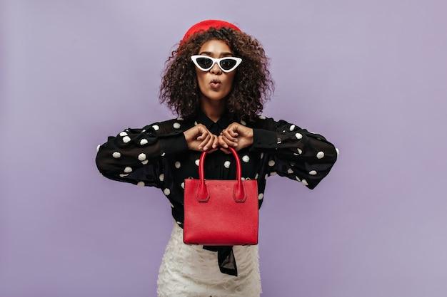 Trendiges lockiges mädchen mit weißer sonnenbrille und roter mütze in langärmeliger bluse, das in die kamera schaut und eine rote handtasche hält holding