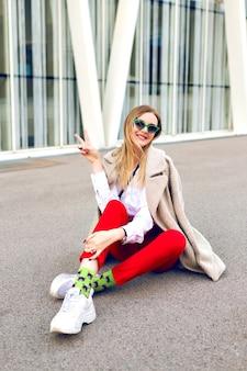 Trendiges modeporträt der stilvollen jungen frau, die nahe modernes architekturgebäude aufwirft, das hipster-geschäftsoutfit und -mantel trägt
