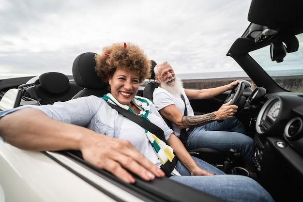 Trendiges seniorenpaar, das sich während der sommerferien im cabrio-auto amüsiert - konzentrieren sie sich auf das gesicht der frau
