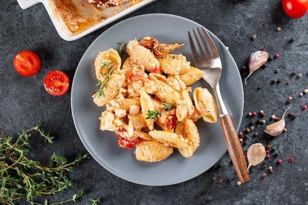 Trendiges virales rezept von gebackenen tomaten und feta mit nudeln. fetapasta auf einem dunklen hintergrund. speicherplatz kopieren. draufsicht.