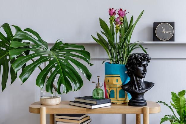 Trendiges wohnzimmerinterieur mit holzkonsole, schönen pflanzen, tropischem blatt, buch, luftpflanze, regal, dekoration, grauer wand, holzpaneelen und persönlichen accessoires im stilvollen hausgarten.