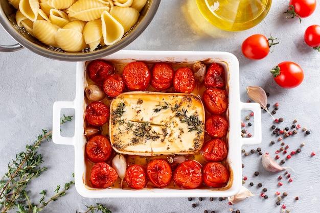 Trending virales rezept von gebackenen tomaten und feta mit nudeln, fetapasta auf einem hellen hintergrund