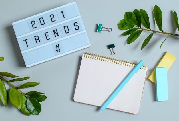 Trendkonzept 2021, leuchtkasten mit inschrift, notizbuchaufzeichnungen, stifte, blume.