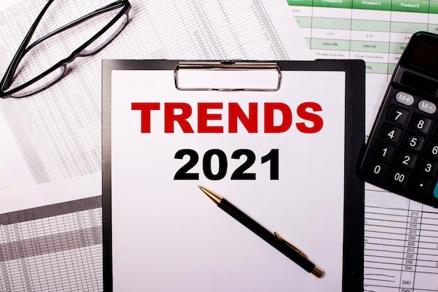 Trends 2021 ist auf ein weißes blatt papier neben der brille und dem taschenrechner geschrieben.
