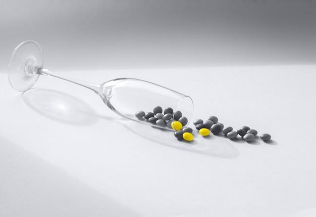 Trendy 2021 ultimate grey und leuchtende farben. stilvolle komposition mit transparentem glasbecher und kleinen bonbons.
