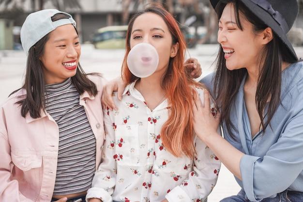 Trendy asiatische mädchen, die spaß zusammen im freien haben
