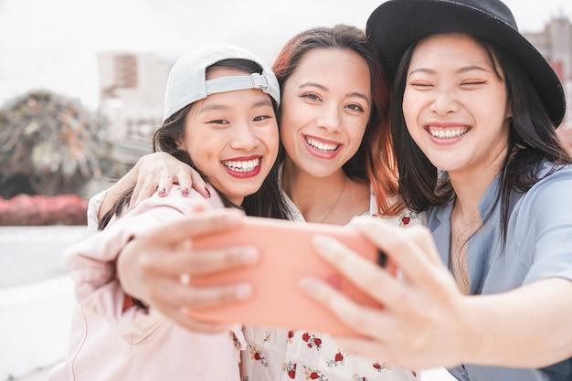 Trendy asiatische mädchen machen video-story für soziale netzwerk-app im freien. junge freundinnen, die spaß haben, selfie zu nehmen