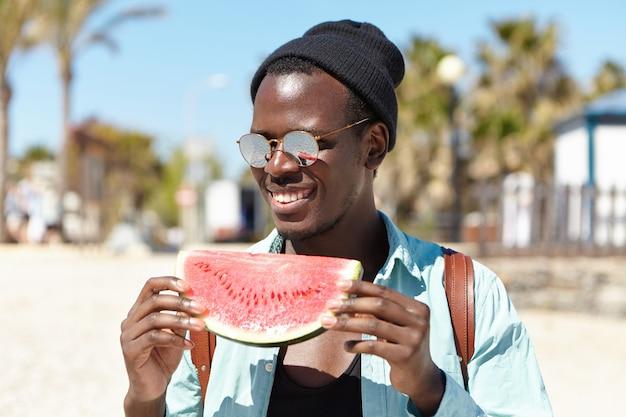 Trendy aussehender fröhlicher junger afroamerikanischer männlicher student, der stilvolle verspiegelte linsenschirme und schwarzen hut trägt, der reife wassermelone isst, während sommertag mit freunden draußen am stadtstrand verbringen