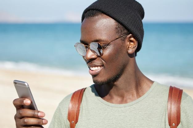 Trendy aussehender junger dunkelhäutiger hipster in verspiegelten linsenschirmen und kopfbedeckungen, der nachrichten liest oder newsfeeds über soziale netzwerke durchsucht, beiträge mag und kommentare hinterlässt, während er sich am strand ausruht