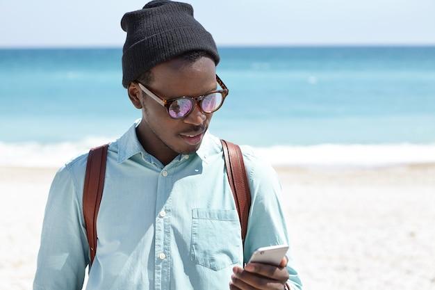 Trendy aussehender junger tourist, der bilder über soziale medien veröffentlicht