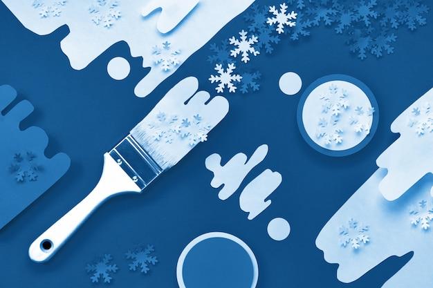 Trendy blauer monochromer weihnachtshintergrund. konzept draufsicht flach lag in klassischer blauer und weißer farbe mit farbe und pinseln, die mit papierschneeflocken beladen wurden.