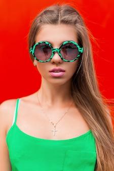 Trendy buntes porträt der hübschen frau in einer modernen grünen sonnenbrille