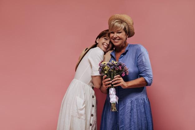 Trendy dame mit blonder frisur im blauen kleid und strohhut lächelnd, hält bunten blumenstrauß und posiert mit mädchen im weißen outfit auf rosa hintergrund.