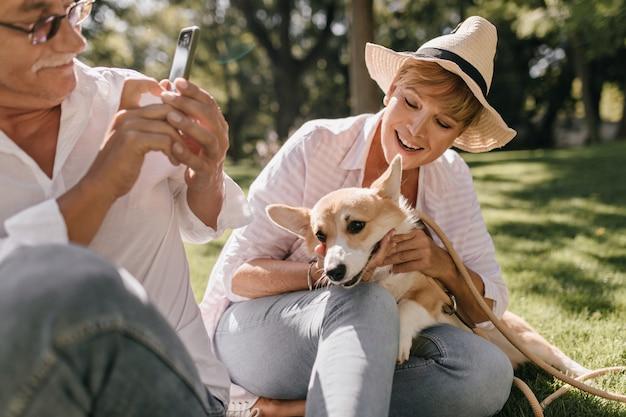 Trendy dame mit kurzen haaren im hut und im rosa hemd lächelnd, sitzend auf gras und posierend mit corgi und mann mit smartphone im park.