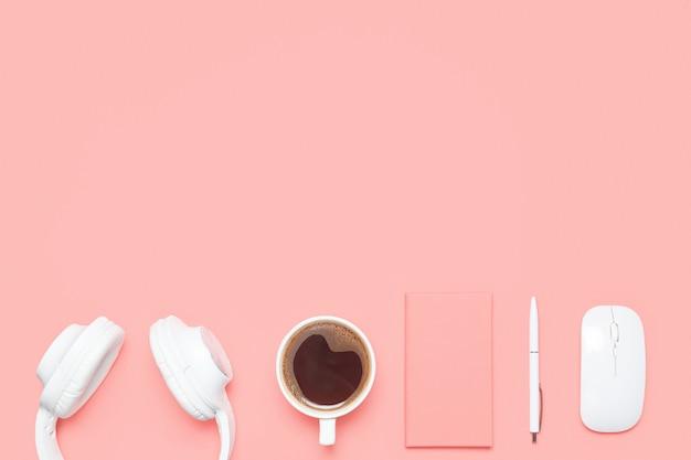 Trendy flaches modell mit kopfhörern, tagebuch, stift, drahtloser maus und tasse kaffee auf korallenfarbenem schreibtisch.