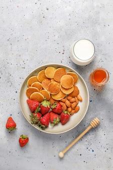 Trendy food - mini-pfannkuchen-müsli. haufen getreidepfannkuchen mit beeren und nüssen.