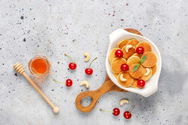 Trendy food - mini-pfannkuchen-müsli. haufen getreidepfannkuchen mit beeren